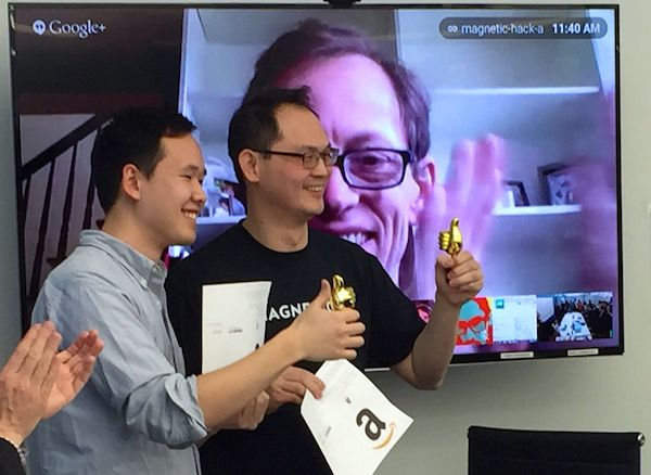 Ed (left) and James receive their prize, while CEO James Green applauds via Google Hangout
